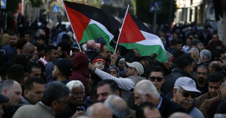 Palestinians wave national flags as they march in the streets of the occupied West Bank city of Ramallah, calling for the cessation of divisions between Fatah and Hamas and the unification of the West Bank and Gaza Strip, on January 12, 2019.