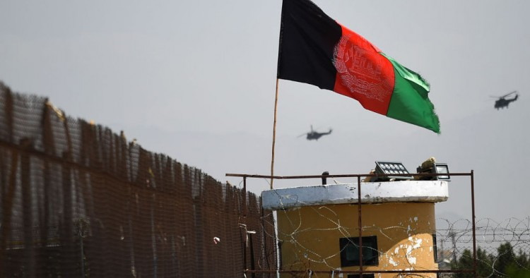 Two US military helicopters are seen flying past an Afghan national flag during the 100th anniversary of the country's Independence Day in Kabul on August 19, 2019.