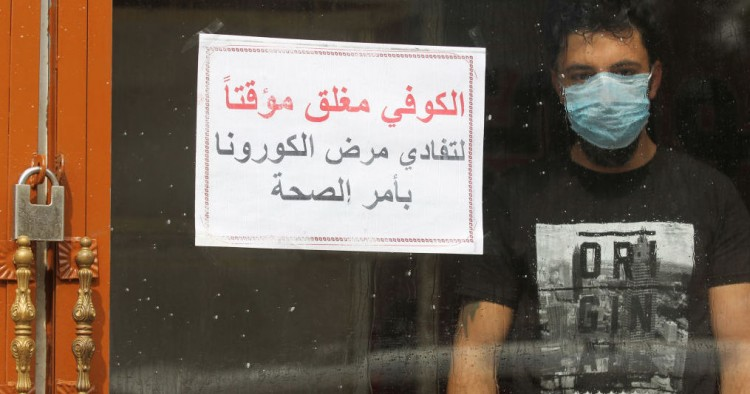 "An Iraqi man, wearing a protective mask, stands inside a coffee shop with a sign in Arabic which reads ""Coffee shop is closed, due to corona following a decision by the Health ministry"" in the capital Baghdad on March 16, 2020 amidst efforts against the spread of COVID-19 coronavirus disease."