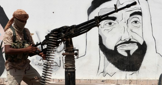 A picture taken on August 8, 2018 during a trip in Yemen organised by the UAE's National Media Council (NMC) shows a soldier loyal to the Saudi and UAE-backed government, manning a machine gun mounted on a vehicle passing by a mural depicting the late UAE founder and president Sheikh Zayed bin Sultan al-Nahyan, along a street in the southeastern port city of Mukalla, the capital of Hadramawt province.