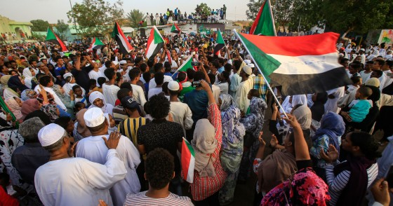 Sudanese people chant slogans and wave national flags as they celebrate after protest leaders struck a deal with the ruling generals on a new governing body, in the capital Khartoum's eastern district of Burri on July 5, 2019, - The deal, reached in the early hours of July 5 after two days of hard-won talks brokered by Ethiopian and African Union mediators, provides for the interim governing body to have a rotating presidency, as a compromise between the positions of the generals and the protesters. The blu