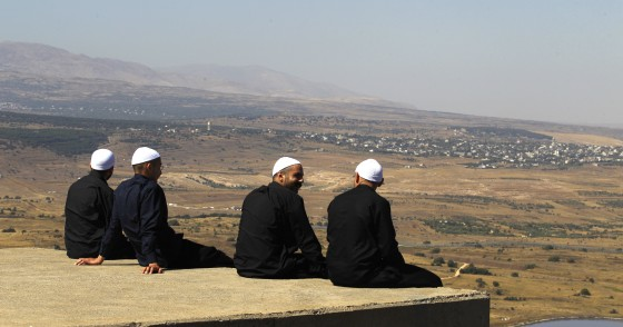 Cover photo: Druze men in the Israeli-annexed Golan Heights look out across the southwestern Syrian province of Quneitra, visible across the border on July 7, 2018. (Photo by JALAA MAREY/AFP/Getty Images)