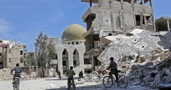 Syrian children ride their bike past destroyed buildings in the former rebel-held town of Zamalka, in Eastern Ghouta on April 5, 2018. / AFP PHOTO / STRINGER (Photo credit should read STRINGER/AFP via Getty Images)