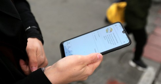 A woman holds a smartphone shown to be unable to access internet, while standing along a street in the Iranian capital Tehran on November 23, 2019.
