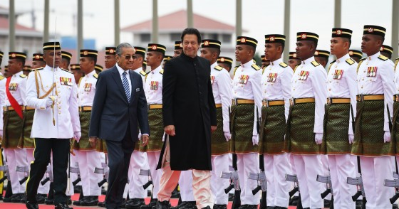 Pakistan's Prime Minister Imran Khan (C) is accompanied by his Malaysian counterpart Mahathir Mohamad (L) as he reviews a guard of honour during a welcoming ceremony at the prime minister's office in Putrajaya on November 21, 2018. (Photo by Mohd RASFAN / AFP) (Photo credit should read MOHD RASFAN/AFP via Getty Images)