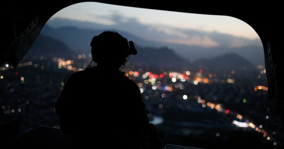 A US Army serviceman sits at the tailgate of an helicopter carrying US Defence Secretary, after leaving the Resolute Support headquarters, in the Afghan capital Kabul on April 24, 2017.