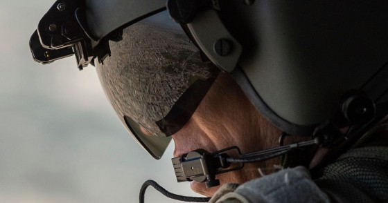A partial view of the Iraqi capital Baghdad is reflected in the visor of a US Army helicopter crew member as he looks out of a Chinook helicopter flying from the US Embassy to Baghdad International airport, following the helicopter of US secretary of State Mike Pompeo, on January 9, 2019.