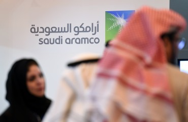 Saudi and Foreign investors stand in front of the logo of Saudi state oil giant Aramco during the 10th Global Competitiveness Forum on January 25, 2016, in the capital Riyadh. The an annual event brings together high-ranking Saudi officials and world business leaders. / AFP / Fayez Nureldine (Photo credit should read FAYEZ NURELDINE/AFP/Getty Images)