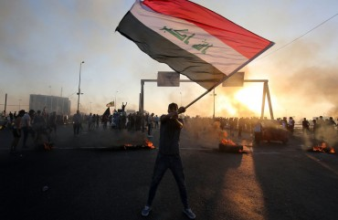 An Iraqi protester waves the national flag during a demonstration against state corruption, failing public services, and unemployment, in the Iraqi capital Baghdad on October 5, 2019.