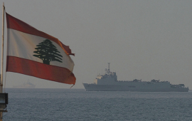 Lebanese flag waving over blue sea with ship