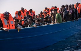Migrants and refugees are assisted by members of the Spanish NGO Proactiva Open Arms as they crowd on board of a wooden boat sailing out of control at 20 miles (38 km) north of Sabratha, Libya on February 18, 2017.