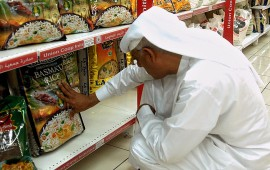 An Emirati man reads the front of a package of Indian Basmati rice in a supermarket in Dubai on July 19, 2008. Faced with the scarcity of fertile land and water, and the surging world prices of food, the wealthy Gulf states are seeking to secure food supplies through agricultural investments abroad.