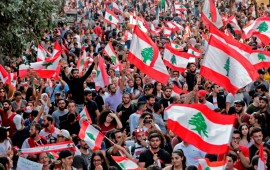 Lebanese protesters wave national flags during demonstrations to demand better living conditions and the ouster of a cast of politicians who have monopolised power and influence for decades, on October 21, 2019 in downtown Beirut.
