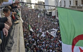 Algerians wave a national flag from a balcony as they watch anti-government demonstrators march in the capital Algiers on December 6, 2019, ahead of the presidential vote scheduled for December 12.