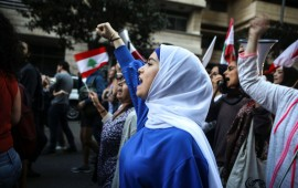 Lebanese anti-government protesters shout slogans as they march on the former demarcation line separating Beirut on December 1, 2019.