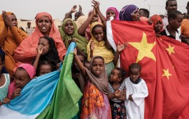 People hold Chinese and Djiboutian national flags as they wait for the arrival of Djibouti's President Ismail Omar Guellehas before the launching ceremony of new 1000-unit housing contruction project in Djibouti, on July 4, 2018. - The new 1000-unit construction project by the Ismail Omar Guelleh Foundation for Housing is financially supported by China Merchant, the operation parther of newly inaugurated Djibouti International Free Trade Zone (DITTZ) with Djibouti Ports and Free Zones Authority, to build ba