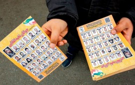 A man standing outside a mosque in the Iranian capital Tehran on February 14, 2020 hands out electoral leaflets showing candidates campaigning in the upcoming Iranian legislative election due to take place on February 21. (Photo by -/AFP via Getty Images)