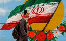 A woman walks past a mural with the Iranian national flag in Tehran, on February 20, 2020 on the eve of parliamentary election.