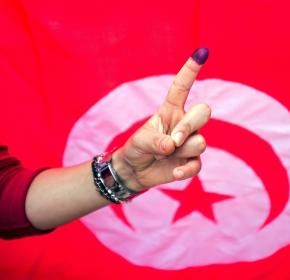 A Tunisian woman shows her ink stained finger after voting at a polling station in Ben Arous,Tunisia, Sunday Oct. 26, 2014.